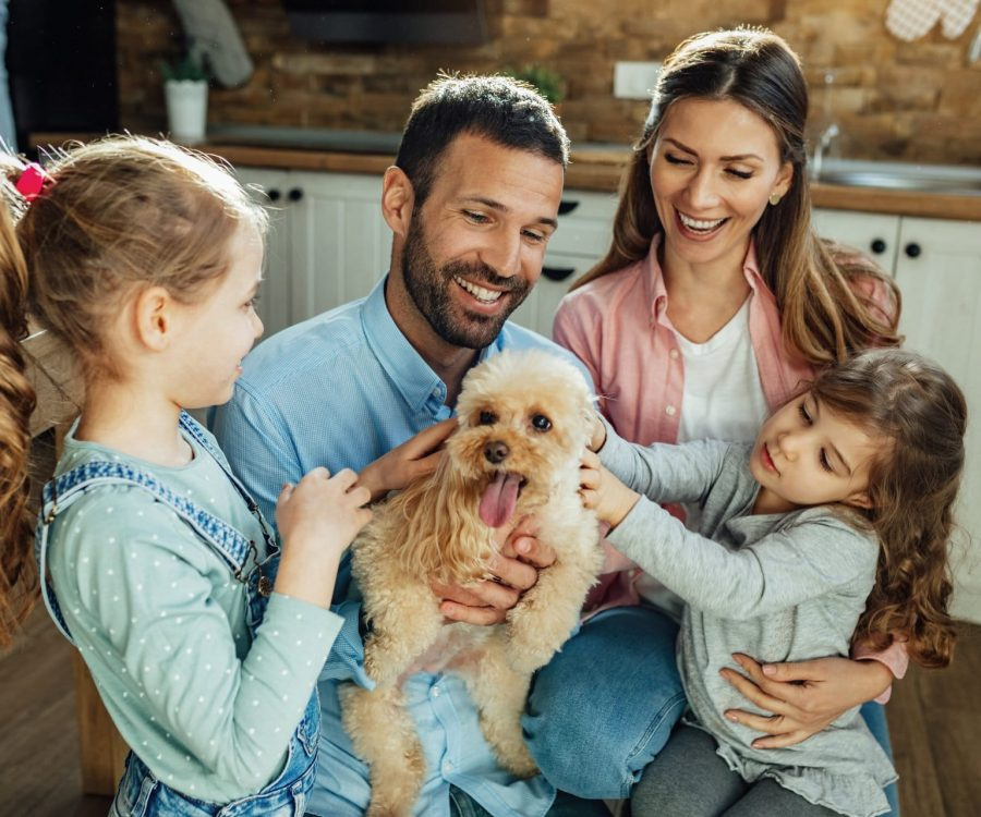 Young happy family having fun with their dog at home.
